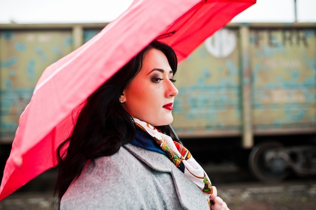 Ragazza castana in cappotto grigio con l'ombrello rosa nella stazione ferroviaria