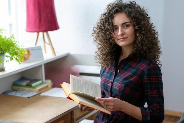 Ragazza castana riccia che tiene un libro in sua mano