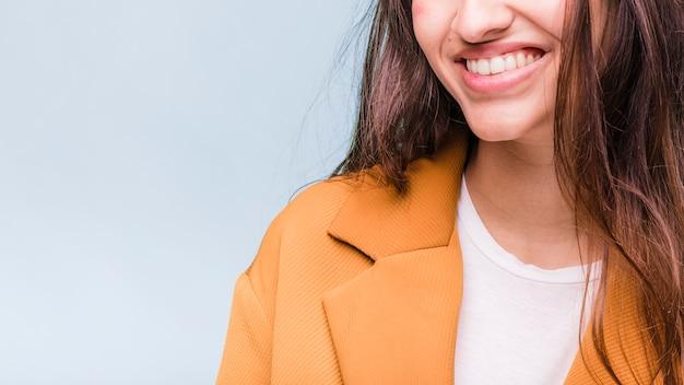 Ragazza castana sorridente che posa con il cappotto