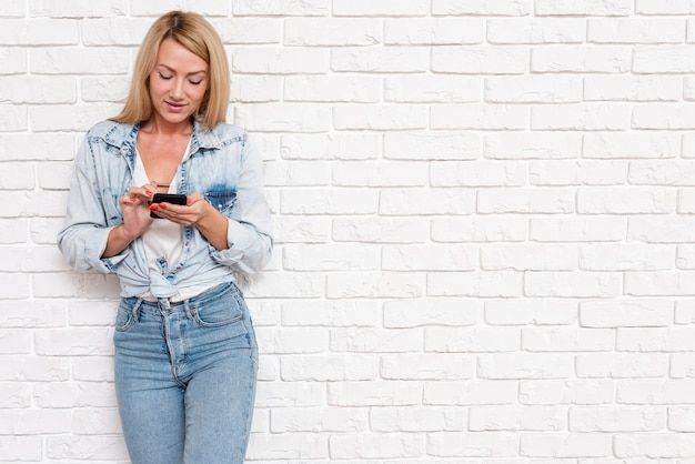 Ragazza casual in denim con telefono