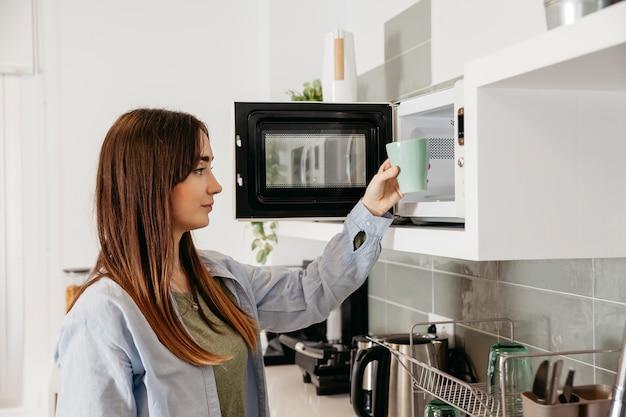 Ragazza casuale facendo uso della microonda per riscaldare tazza