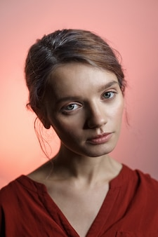 Ragazza caucasica abbastanza sensuale in camicia rossa che esamina la macchina fotografica e che inclina la sua testa. ritratto di bellezza su sfondo rosa
