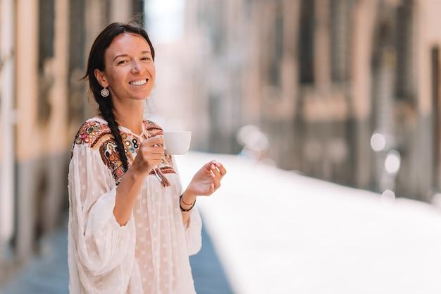 Ragazza caucasica che beve il caffè caldo della bevanda che cammina in via all'europa