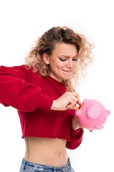 Ragazza caucasica con capelli biondi ricci che cercano di ottenere soldi dal salvadanaio rosa del maiale, ritratto isolato su bianco
