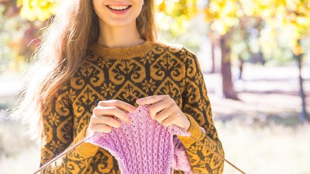 Ragazza caucasica con capelli lunghi in un maglione marrone sorridente