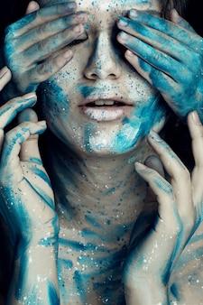 Ragazza caucasica con la faccia dipinta in fiori bianchi blu