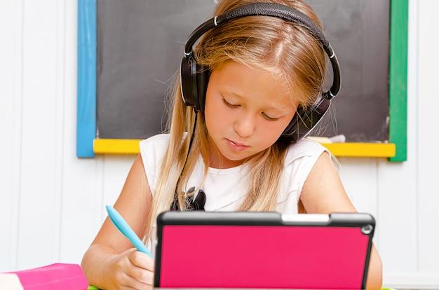 Ragazza caucasica con le cuffie che ascolta e che scrive. istruzione domestica e istruzione a distanza