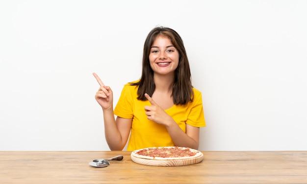 Ragazza caucasica con una pizza che punta il dito verso il lato