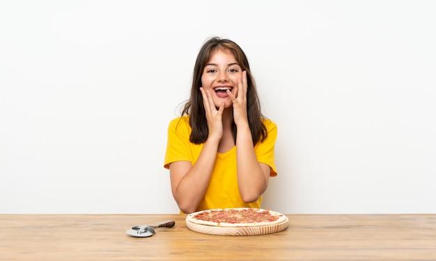 Ragazza caucasica con una pizza con espressione facciale a sorpresa