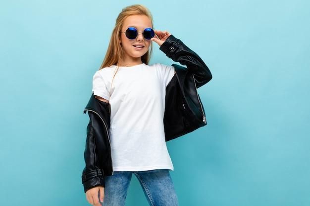 Ragazza caucasica dell'adolescente con capelli marroni lunghi in balli neri dei jeans del denim e della giacca isolati su fondo blu