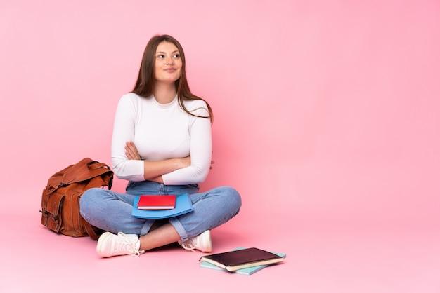 Ragazza caucasica dello studente dell'adolescente che si siede sul pavimento isolato sul cercare rosa mentre sorridendo