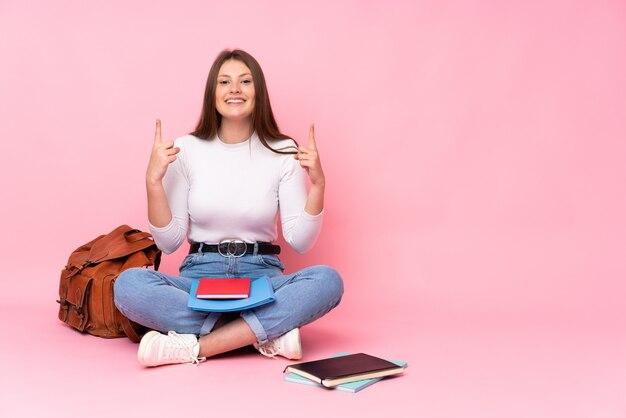 Ragazza caucasica dello studente dell'adolescente che si siede sul pavimento isolato sulla parete rosa che indica su una grande idea