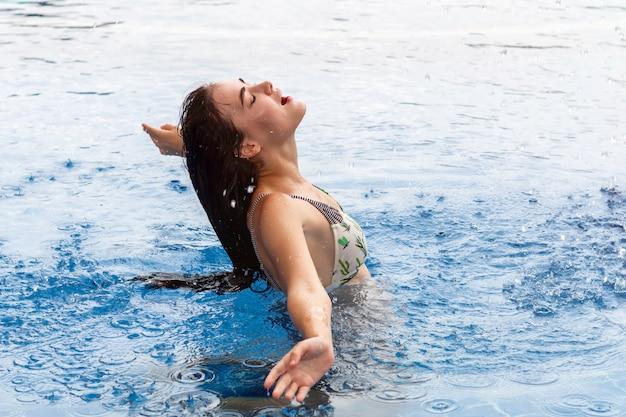 Ragazza caucasica di bellezza che spruzza acqua con i suoi capelli nello stagno.