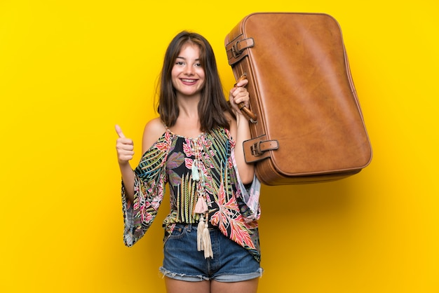 Ragazza caucasica in abito colorato sul muro giallo isolato in possesso di una valigetta vintage