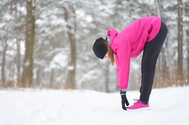 Ragazza caucasica in attrezzatura sportiva rosa che allunga su nella foresta nevosa di inverno prima del pareggiare.