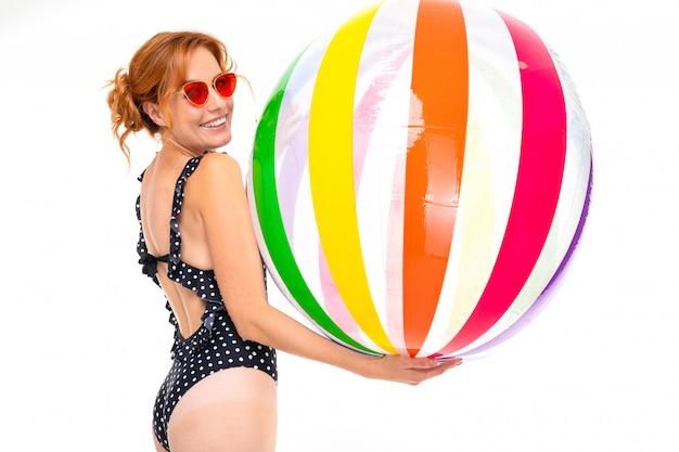Ragazza caucasica in retro costume da bagno e occhiali da sole con la palla di acqua a strisce su bianco