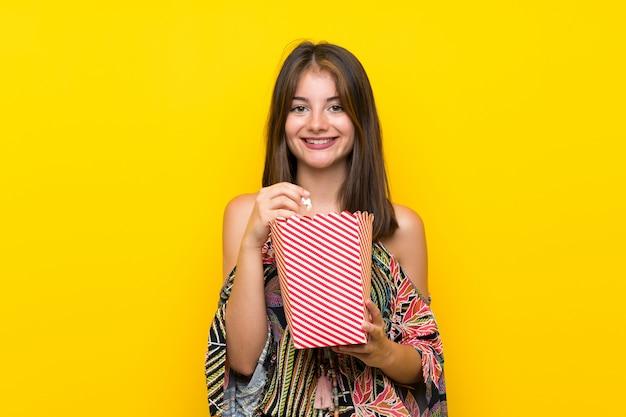 Ragazza caucasica in vestito variopinto sopra la parete gialla isolata che mangia i popcorn