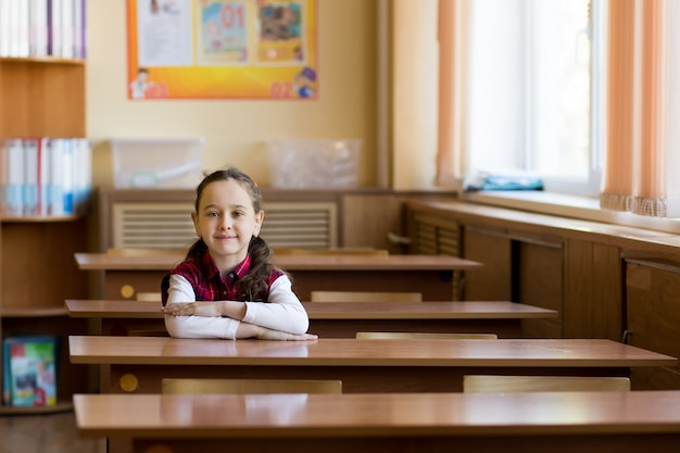 Ragazza caucasica sorridente che si siede allo scrittorio nella stanza di classe
