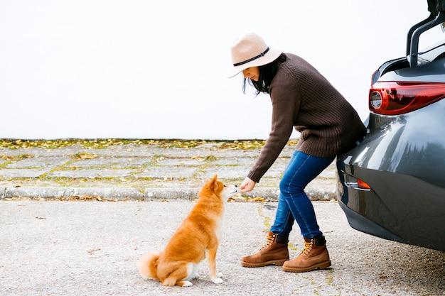 Ragazza caucasica spagnola che si siede sull'automobile che dà un premio al suo cane