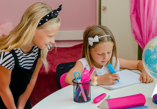 Ragazza caucasica wathching sua sorella minore disegno con pennarello. concetto di relazioni familiari.