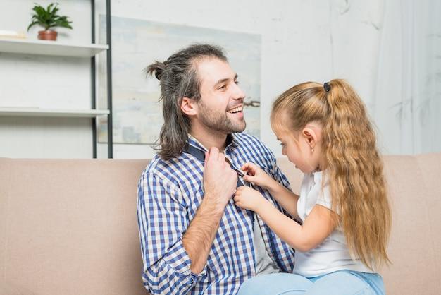 Ragazza che abbottona la camicia di suo padre