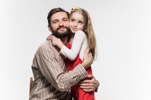 Ragazza che abbraccia suo padre sopra un bianco