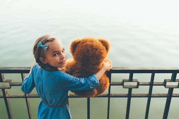 Ragazza che abbraccia un orsacchiotto carino guardando sopra la spalla