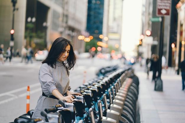 Ragazza che affitta una bici da città da un cavalletto