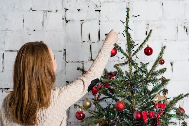 Ragazza che appende le sfere rosse sull'albero di natale. natale e il concetto di capodanno.