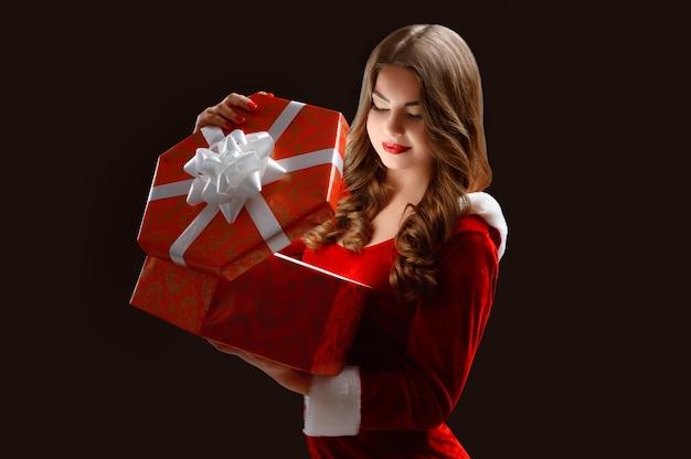 Ragazza che apre un grande regalo per le feste di capodanno e chistmas.