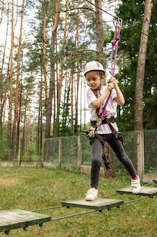 Ragazza che arrampica un percorso in una corda del parco