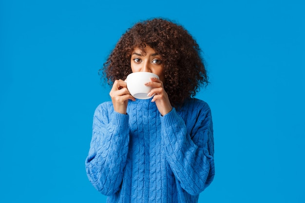 Ragazza che ascolta i pettegolezzi freschi e sorseggiando tè. bella donna afroamericana incuriosita e rilassata che ha le amiche che si incontrano, bevendo caffè dalla tazza e sembrando interessata