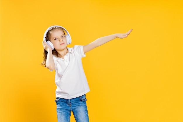 Ragazza che ascolta la musica in cuffie senza fili. ragazza danzante. piccola ragazza felice che balla alla musica. bambino sveglio che gode della musica da ballo felice.