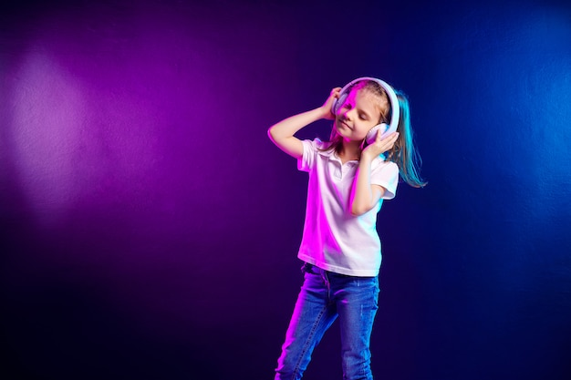 Ragazza che ascolta la musica in cuffie su colorato scuro. bambino sveglio che gode della musica da ballo felice, dell'occhio vicino e della posa di sorriso
