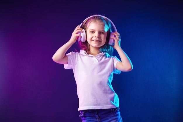 Ragazza che ascolta la musica in cuffie su colorato scuro. bambino sveglio che gode della musica da ballo felice e posa di sorriso