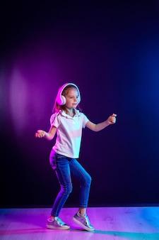 Ragazza che ascolta la musica in cuffie su colorato scuro. ragazza danzante. piccola ragazza felice che balla alla musica. bambino sveglio che gode della musica da ballo felice.