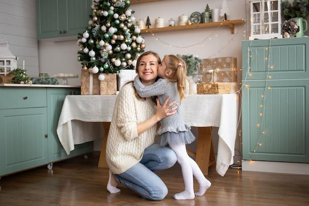 Ragazza che bacia sua madre nella cucina di natale a casa.