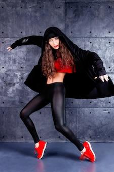 Ragazza che balla davanti al muro urbano.