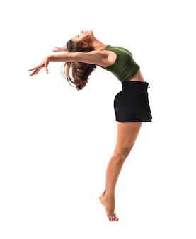 Ragazza che balla e che salta nello studio su fondo isolato