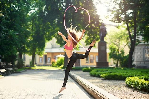 Ragazza che balla facendo piroette con un nastro nel parco cittadino.