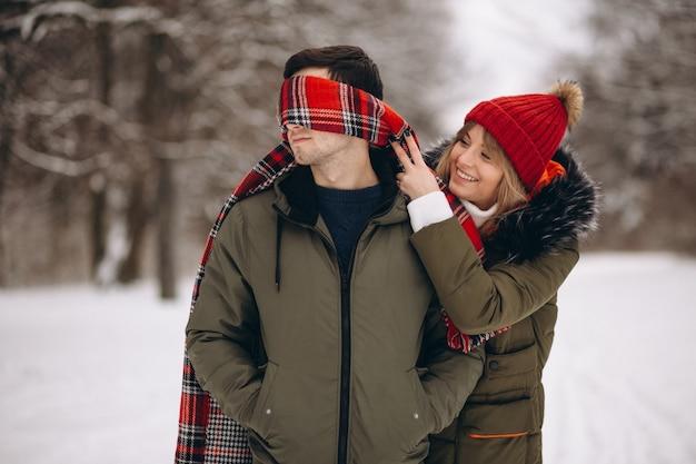 Ragazza che benda l'uomo sul san valentino in un parco di inverno