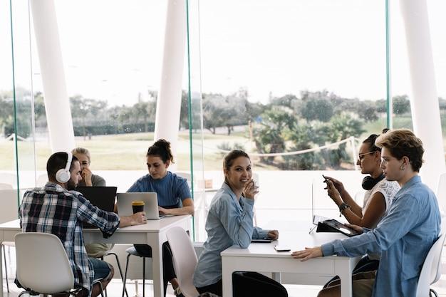 Ragazza che beve caffè e in attesa di sedersi a un tavolo con persone che lavorano in un coworking