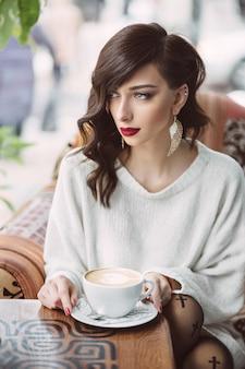 Ragazza che beve caffè in un caffè alla moda