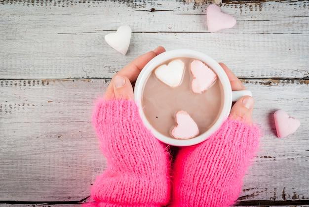 Ragazza che beve cioccolata calda con i cuori delle caramelle gommosa e molle