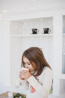 Ragazza che beve da un bicchiere di succo o bevanda, ghirlande e abili, la stanza è decorata per natale