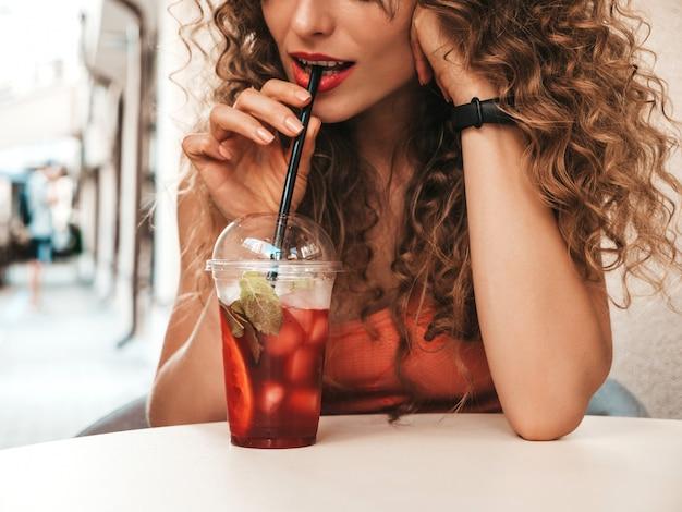 Ragazza che beve frullato fresco in tazza di plastica con paglia