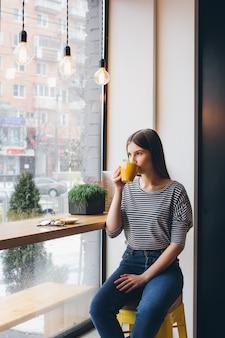 Ragazza che beve il caffè in una caffetteria