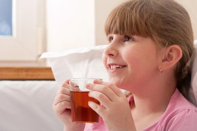 Ragazza che beve il tè mentre era seduto nel letto. ambientazione interna. avvicinamento.