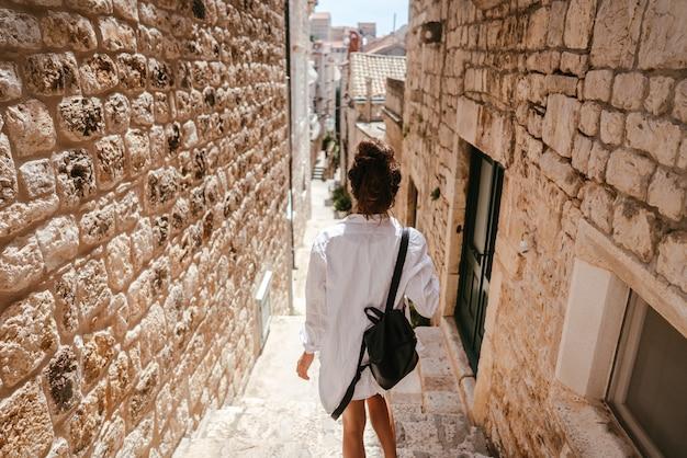 Ragazza che cammina attraverso antiche stradine in una bella giornata estiva