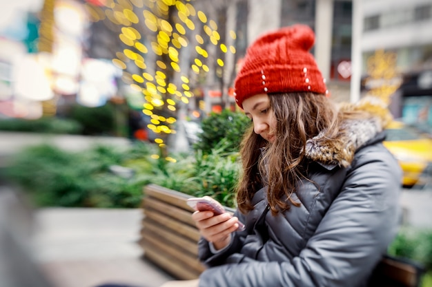 Ragazza che cammina e manda un sms sul suo smartphone
